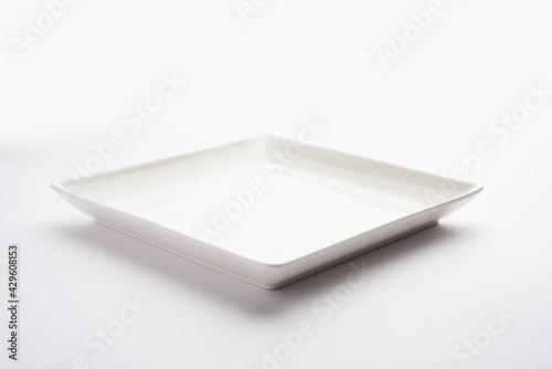 Fototapeta Empty white ceramic square plate isolated on white