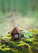 Toy House On Moss, Green Natural Forest Background. Symbol Of Family, Mortgage, Real Estate Concept. Eco Friendly House