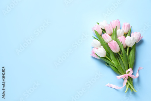Obraz Beautiful pink spring tulips on light blue background, top view. Space for text - fototapety do salonu