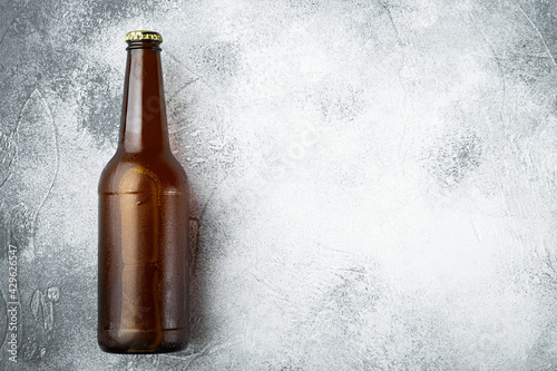 Fotografiet Beer bottle, on gray stone background, top view flat lay, with copy space for te
