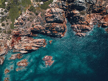 Aerial View Of A Breathtaking And Wild Coastline Characterised By Reddish Cliffs And A Turquoise Transparent Sea In Isola Rossa, Sardinia, Italy.