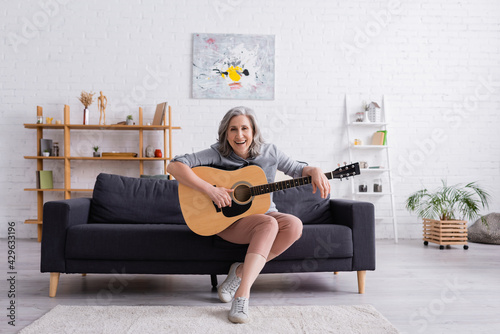 Fotografija cheerful mature woman with grey hair sitting on couch with acoustic guitar