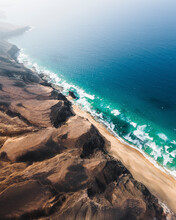 Aerial View Of Wild Coastline With Waves Breaking On The Shore In Playa De Cofete, Pajara, Canary Islands, Spain.
