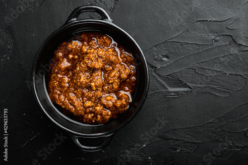 Fotografie, Obraz Red pesto italian sauce, in bowl, on black stone background, top view flat lay,
