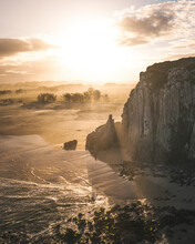 Aerial View Of Sunlight Rays Shining Through Trees And Seaside Rock Formation At Sunset In Torres, Rio Grande Do Sul, Brazil.