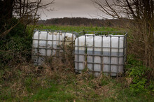 Two Large Water Bowser Tanks Sitting At The Edge Of A Farmers Field