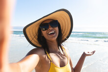 Smiling Mixed Race Woman Wearing Sunhat And Sunglasses Taking Selfie On Beach