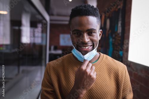 Obraz na plátně Portrait of happy african american businessman taking off face mask standing in