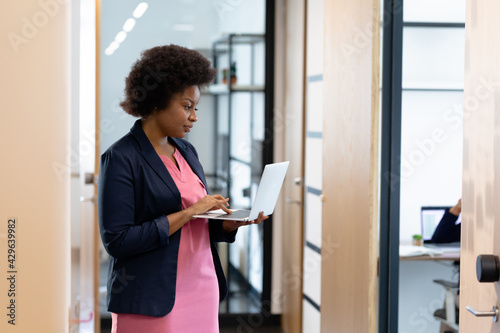 Smartly dressed african american businesswoman standing in corridor using laptop - fototapety na wymiar