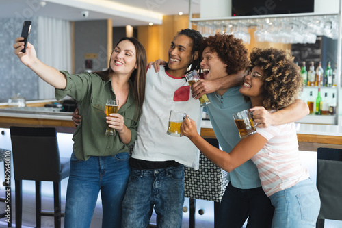 Diverse group of male and femalefriends raising glasses and taking selfie at bar