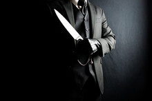 Portrait Of Man In Dark Suit And Leather Gloves Holding Sharp Knife. Well Dressed Mafia Hit Man. Gentleman Assassin.