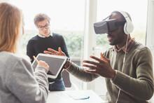 Three Millennials Multiethnic Businesspeople Using 3D Viewer