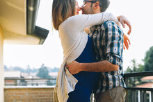Happy Young Pregnant Couple In Love Outdoors Hugging And Kissing