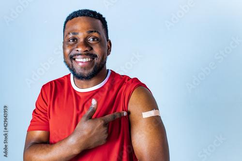 Murais de parede afro american sportsman showing his arm after receiving a vaccine in studio