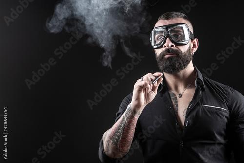 Obraz na plátně Uomo moro con la barba occhiali da motociclista,  fuma una sigaretta e produce u