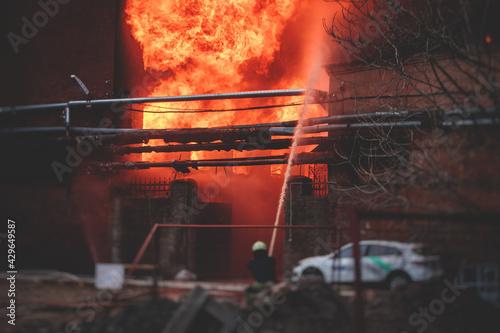 Fotografie, Obraz Firefighters put out large massive fire blaze, group of fire men in uniform duri