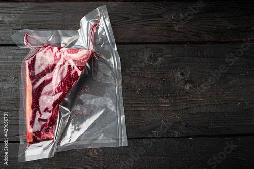 Fotografie, Tablou T-bone or florentine dry aged  raw marbled beef steak in vacuum packaging, on bl