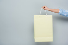Partial View Of Woman With Shopping Bag On Grey Background With Copy Space