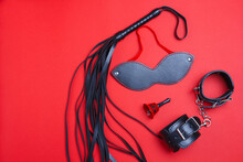 Whip And Mask, Bell And Handcuffs For BDSM Role-playing Games. Sex Shop Is Having Fun As A Punishment, Passionately Spank Black Objects With Closed Eyes On A Red Background.