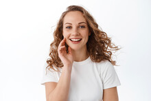 Attractive Young Woman Touching Natural Face Without Make Up, Smiling Pleased And Looking At Camera, Standing In T-shirt Against White Background