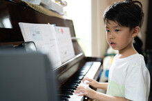 A Boy Is Studying Piano Online With Tablet.