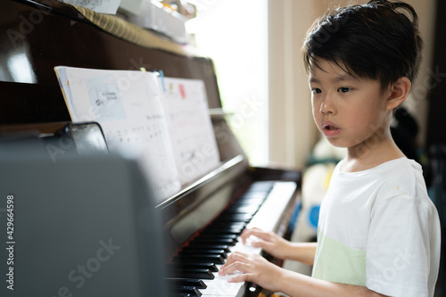 Fotografie, Obraz A boy is studying piano online with tablet.