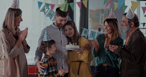 Fototapeta Happy multi-generation family of four members celebrating birthday party with candle cake blowing and enjoying reunion holiday. obraz