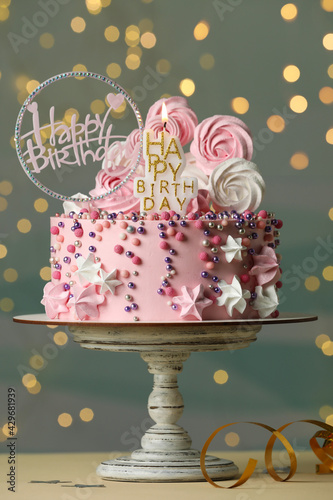 Obraz Beautiful birthday cake with festive decor and candle on white table - fototapety do salonu