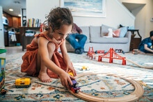 Girl Playing With Toy Train In Living Room