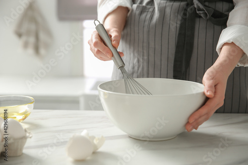 Fotografie, Obraz Woman making dough at table in kitchen, closeup