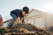 Happy Boy Digging In Pile Of Dirt