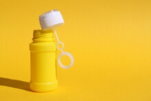 Yellow Bottle For Soap Bubbles Stands On Yellow Background With Place For Text