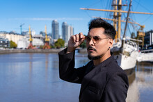 Medium Shot Of Young Latino In Sexy Pose Taking Sunglasses On A Bridge With An Old Ship Behind. Sexy, Daring Concept.