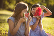 Two little girls spending time outside and eating watermelon. Focus is on background.