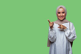 Beautiful indonesian woman wearing hijab is pointing to the left side with smiling
