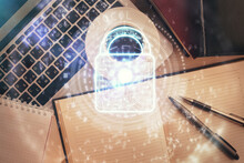 Double Exposure Of Lock Hologram Drawing Over Study Table Background With Computer. Concept Of Data Security. Top View.
