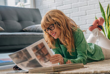 Woman Photographer At Home Looking At Photo Album