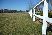 A White Fence With Green Gardens . Horse Racecourse Field . Large Farmland And Ranch Protection Background . Green Pastures Of Horse Farms. Country Summer Landscape. White Fence Is A Long Way.