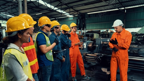 Fotografia Skillful worker attending brief meeting in the factory
