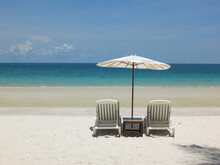 White Beach Bed With White Umbrellas Rests On White Sand, Sea Front And Blue Sky.