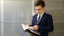 School Boy In Eyegasses Is Holding A Book And Turn On The Pages.