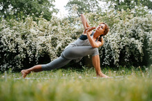 Young Attractive Woman Performs Exercises With Her Own Weight On The Background Of Greenery In The Park. Yoga Pose For Stretching.