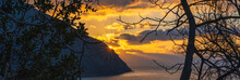 Panoramic View Of Sunrise Over The Sea Through The Branches Of Trees. The Sun Rises From Behind The Mountain, And Its Yellow Rays Illuminate The Sky And The Sea.
