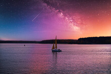 A Small Sailboat Floats On The Lake Against The Backdrop Of A Picturesque Evening Sky.