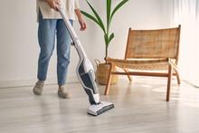 Anonymous Woman Vacuuming Floor In Modern Minimalist Apartment