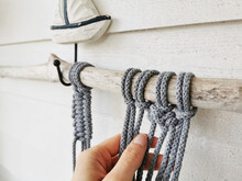 Woman's Hand Making Crochet From Grey Cotton Yarn Wall Hanging With A Boat Sculpture On It