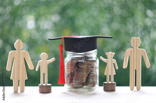 Obraz Graduation hat on glass bottle with model family and stack of coins money on natural green background, Saving money for education and family finance concept - fototapety do salonu