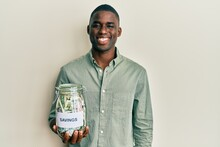 Young African American Man Holding Jar With Savings Looking Positive And Happy Standing And Smiling With A Confident Smile Showing Teeth