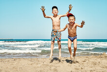 Funny Joyful Little Brothers Jump On Sand Beach Against Sea