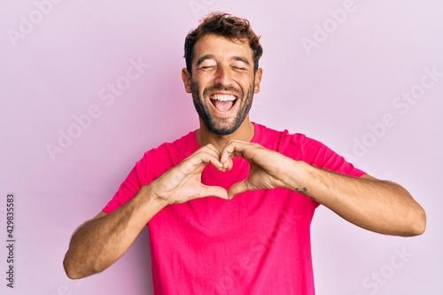 Billede på lærred Handsome man with beard making heart symbol with hands shape smiling and laughing hard out loud because funny crazy joke